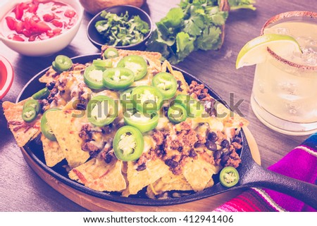 Claasic nachos with ground beef and fresh jalapeno chile peppers. - stock photo