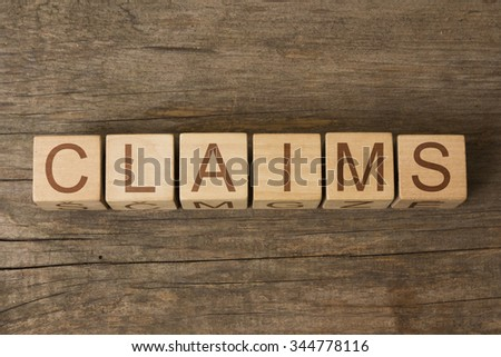 CLAIMS text on a wooden background - stock photo