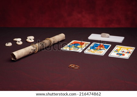Clairvoyance equipment with weddings rings on dark desk - stock photo