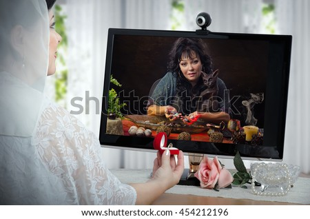 Clairvoyant uses energy of semi-precocious gemstones for charging wedding rings during on-line video session. Bride in white dress sits opposite a monitor and holds small red box with two rings