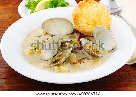Clam chowder served with fragrant cheddar cheese biscuit that will warm the heart on a cool fall or cold winters day - stock photo