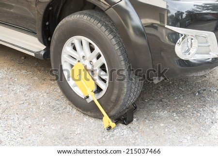 clamped front wheel of illegally parked car  - stock photo