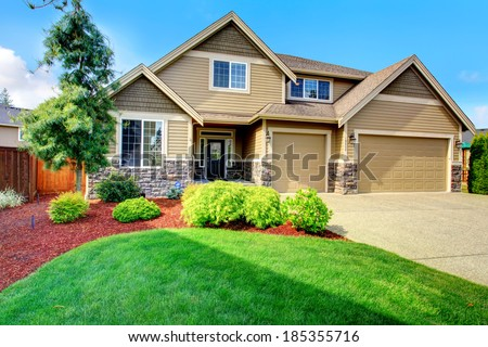 Clapboard siding house  with stone trim. View of  entrance porch, beautiful flower bed with green lawn, bushes and fir tree