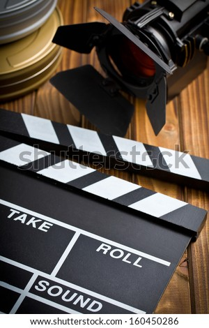 clapper board with movie light on wooden table - stock photo