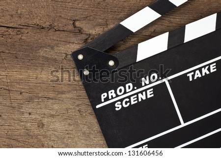 Clapperboard lying on wooden background.