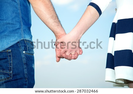 Clasped hands of a young romantic man and woman against a blue sky with copy space. Conceptual image of love, friendship. Love Story. Concept shoot of friendship and love of man and woman: two hands