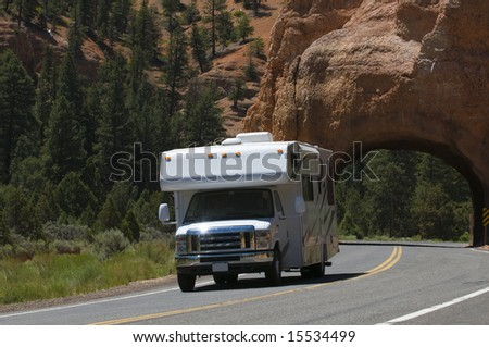 Class C RV recreational vehicle driving past natural red rock tunnel