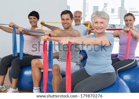 Class holding out exercise belts while sitting on fitness balls in yoga class - stock photo