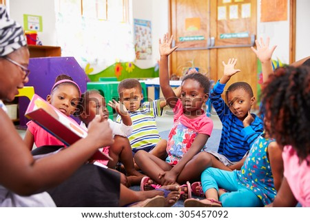 Class of preschool children raising hands to answer teacher - stock photo