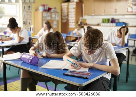 Class of primary school kids studying during a lesson, close up