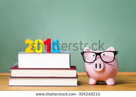 Class of 2016 theme with textbooks and piggy bank with glasses on green chalkboard background - stock photo