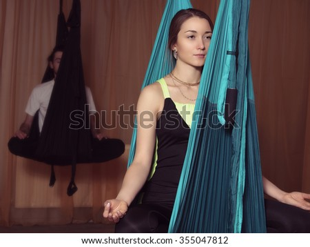 Classes in yoga fly. A girl sits in a hammock with her legs crossed and meditates