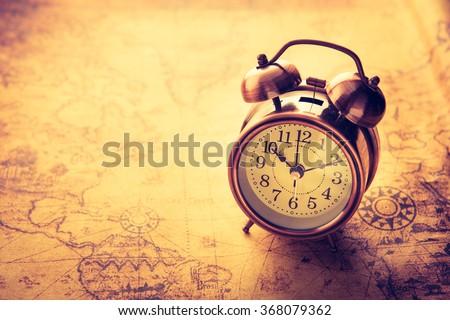 Classic Alarm clock on vintage map background,vintage process tone style - stock photo