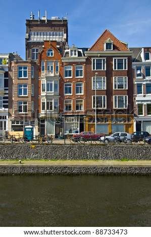 Classic amsterdam view. Residential homes on the canal. Urban scene. Spring. - stock photo
