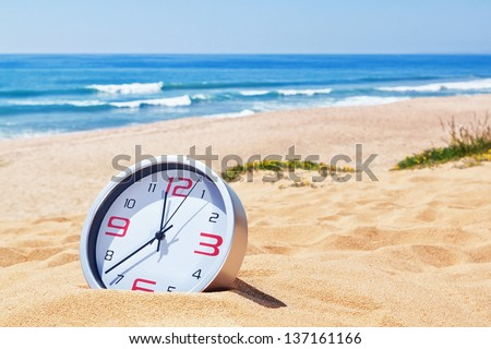 Classic analog clocks in the sand on the beach near the sea. For the holidays. - stock photo