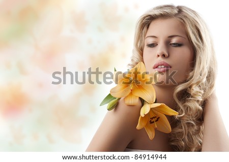 classic beauty portrait of young and beautiful blonde girl with orange lily and blond curly hair over white - stock photo
