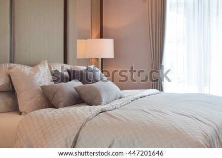 Classic bedroom interior with pillows and reading lamp on bedside table - stock photo