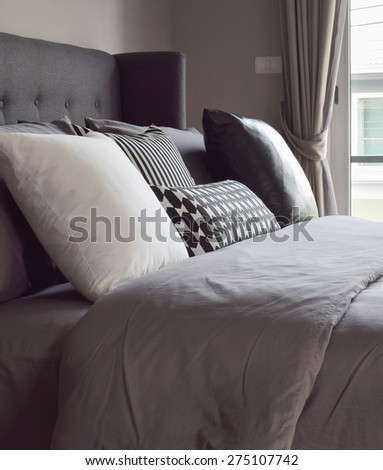 Classic bedroom interior with pillows next to the window - stock photo