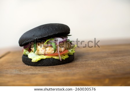 Classic black Burger. Tasty and fastfood burger meal on the table - stock photo