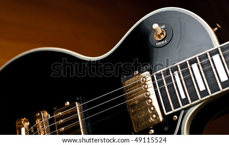 Classic black Les Paul style rock and roll or jazz guitar in soft spotlight. Stage or studio concept ready to perform. - stock photo