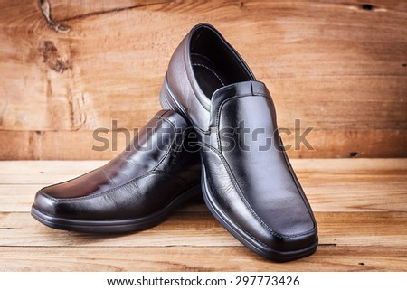 Classic black men's shoes on wood background - stock photo