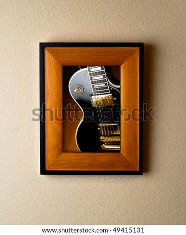 Classic black rock guitar image in wooden frame on wall. Unique image demonstrates musical memories or instrument collector concept. - stock photo