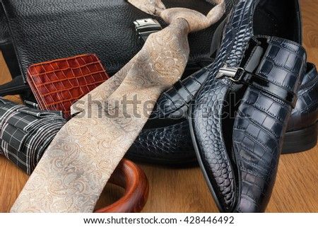 Classic blue shoes, tie, umbrella and briefcase on the wooden floor, can be used as background - stock photo