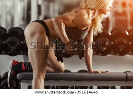 Classic bodybuilding. Muscular blonde fitness woman doing exercises in the gym. Fitness woman in the gym. Bodybuilder woman in the gym. Fitness woman with dumbbell. - stock photo