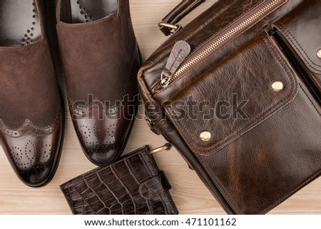 Classic brown shoes, briefcase and purse on the wooden floor, can be used as background