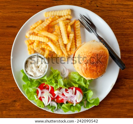 classic burger with French fries on the table in a cafe - stock photo