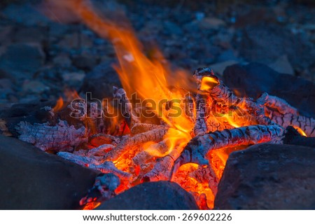 Classic camping campfire in rock fire ring at dusk closeup - stock photo