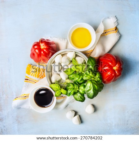 classic caprese salad ingredients, composing on blue wooden background, top view - stock photo