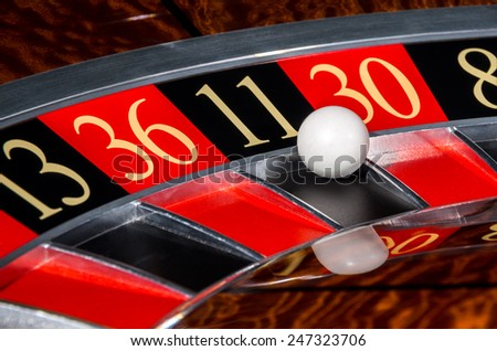 Classic casino roulette wheel with black sector eleven 11 and white ball and sectors 13, 36, 30, 8 - stock photo