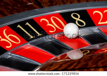 Classic casino roulette wheel with lucky red sector thirty 30 and white ball and sectors 36, 11, 8, 22 - stock photo