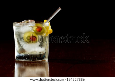 classic cocktail served  on the rocks with pimento stuffed cocktail olives and a lemon twist