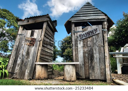 Classic country outhouse toilets with waiting area provided - stock photo