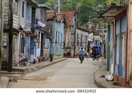 Classic cuban backstreet with bike and rickshaw - stock photo