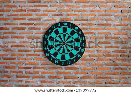Classic darts board on brick wall texture background