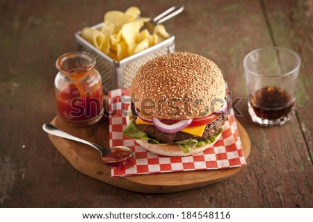 Classic deluxe cheeseburger with lettuce, onions, tomato and pickles on a sesame seed bun - stock photo