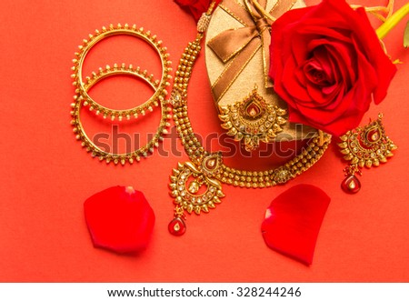 Classic design of an Indian gold necklace and bangles set arranged with heart shaped gift box and red rose flowers. - stock photo