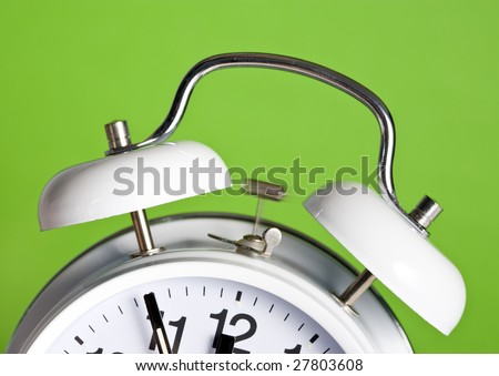 classic double bell alarm clock ringing at 5 minutes to 12 - stock photo