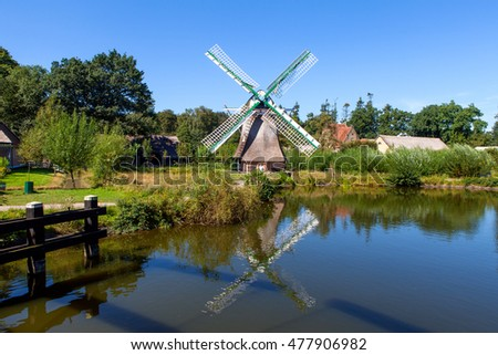 Classic Dutch windmill in nature with blue sky in the background