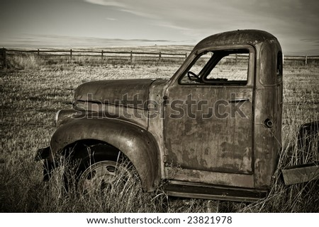 Classic farm truck left rusting in the field - stock photo