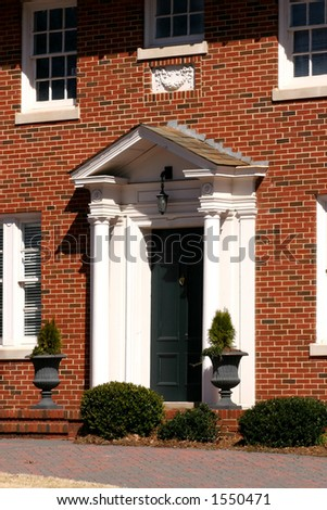 Classic front door with small porch and columns - stock photo