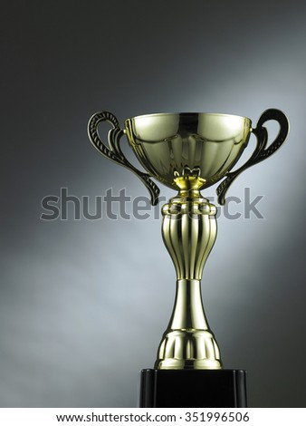 classic golden trophy on the gray background with light effect - stock photo