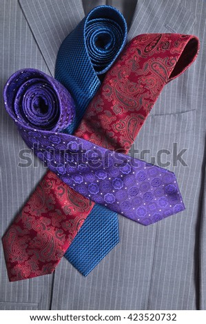 Classic gray striped business suit with purple, red, and blue ties on top. Fashion and classic trends  - stock photo