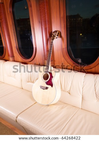 Classic guitar on leather sofa - stock photo