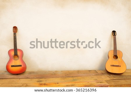 classic guitars propped in front of a white wall as background