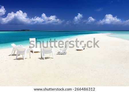classic idyllic beach with white sunbeds near sea and sand - stock photo