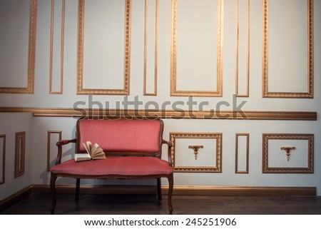 Classic interior design. Elegant red vintage couch with an open book on it standing against white wall with golden moldings - stock photo